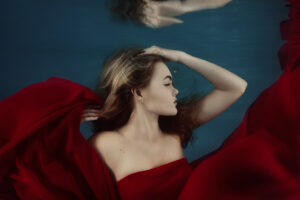 Underwater portrait of a beautiful young woman, head and shoulders, side profile, with flowing red dress, water reflections above