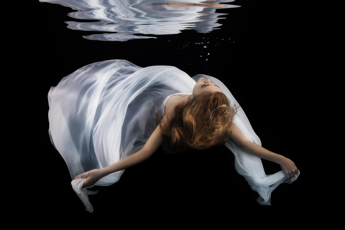 Underwater portrait of a beautiful bride in white gown sinking back down through the water, arms outstretched, black background, trash the dress shoot