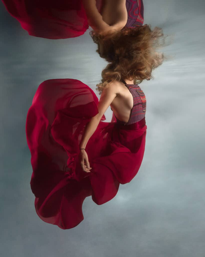 Underwater portrait of red-blonde hair young woman wearing red chiffon dress, floating hair and fabric