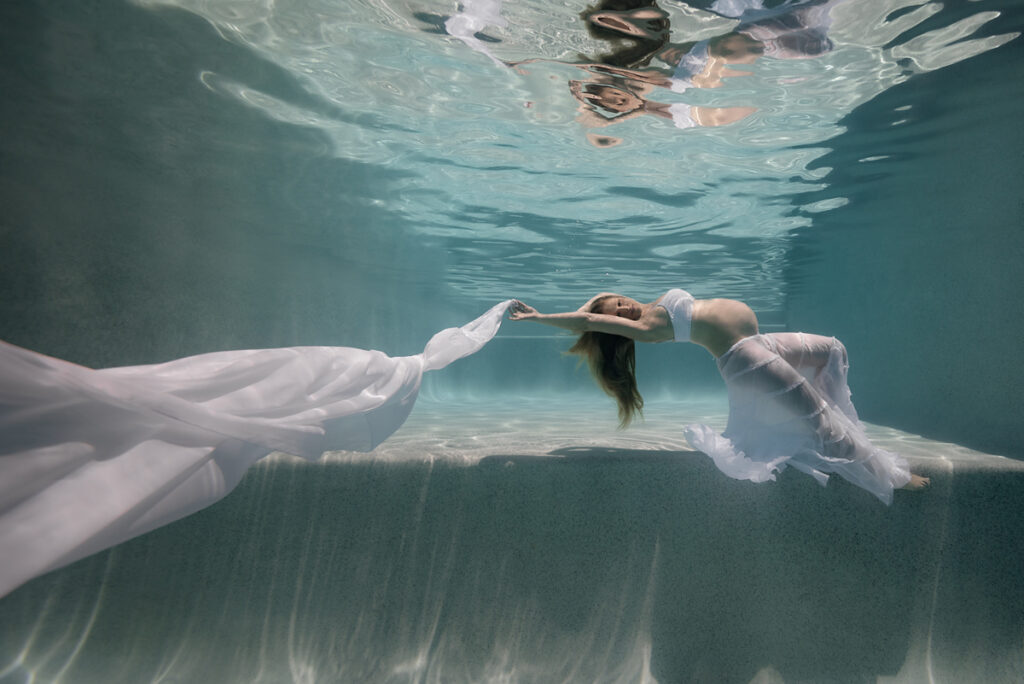 Underwater maternity portrait of a pregnant lady in a large swimming pool, wearing flowing white skirt and draping a long white chiffon scarf.