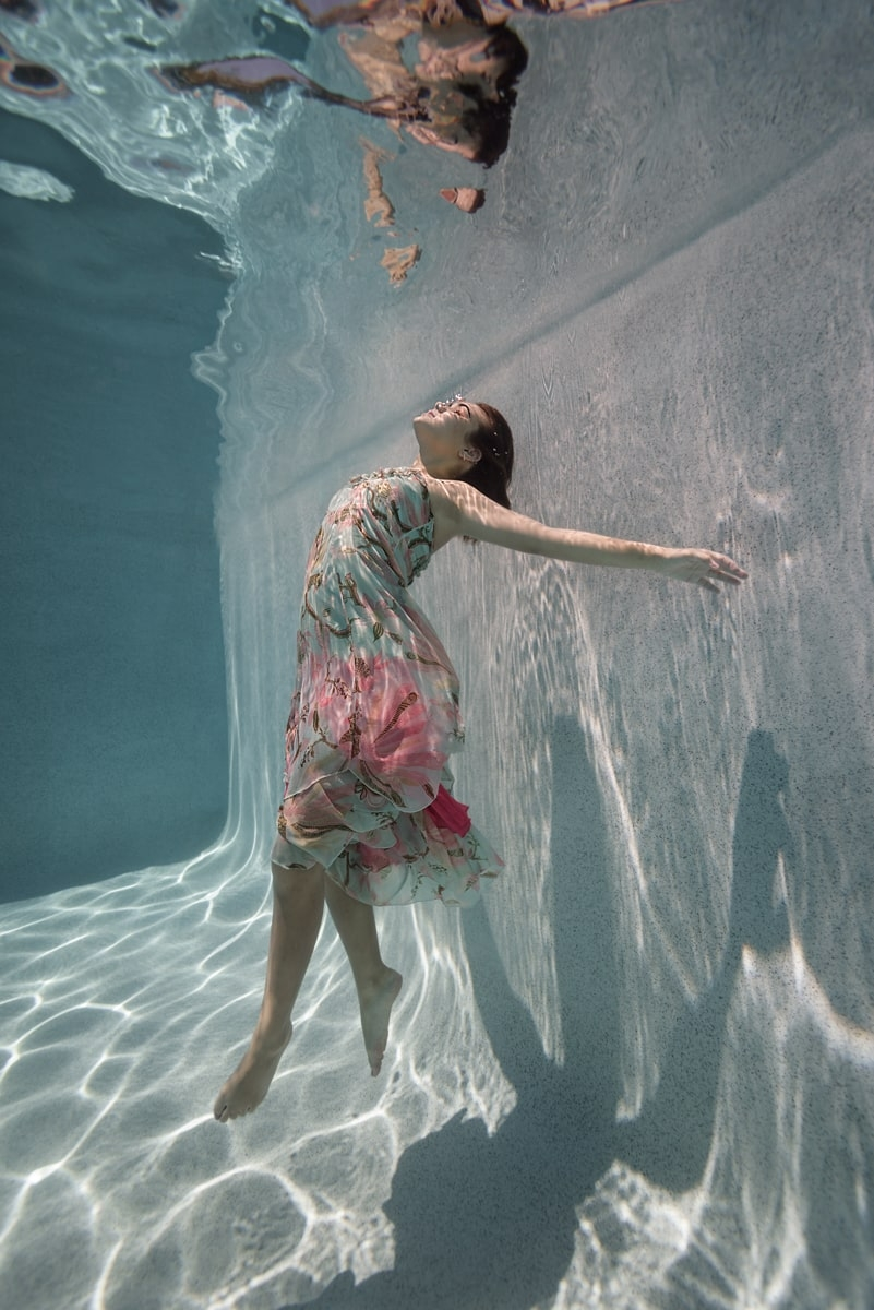 Underwater pool portrait of young woman wearing pastel floral chiffon dress, arched back, driting up toward the surface