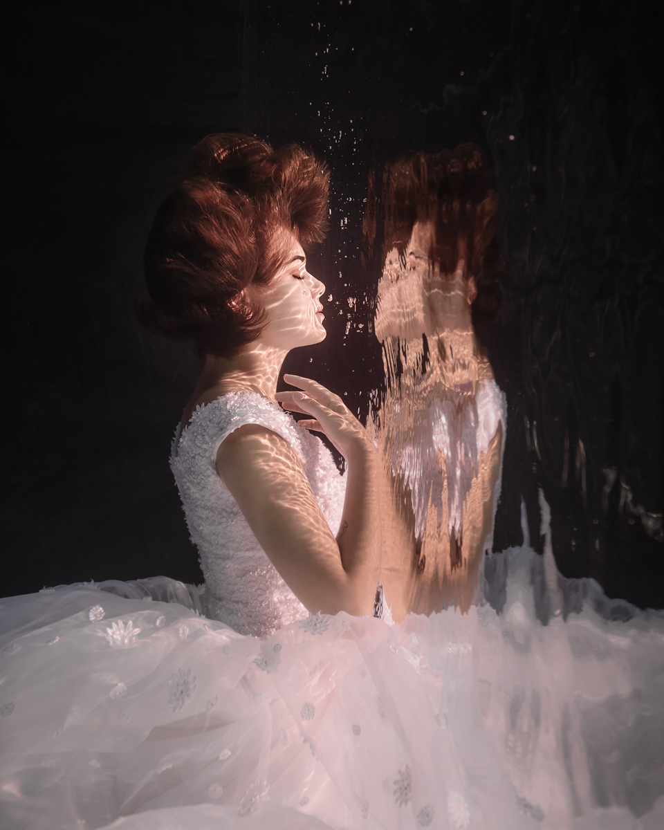woman underwater wearing a wedding dress, black background, bubbles and reflections