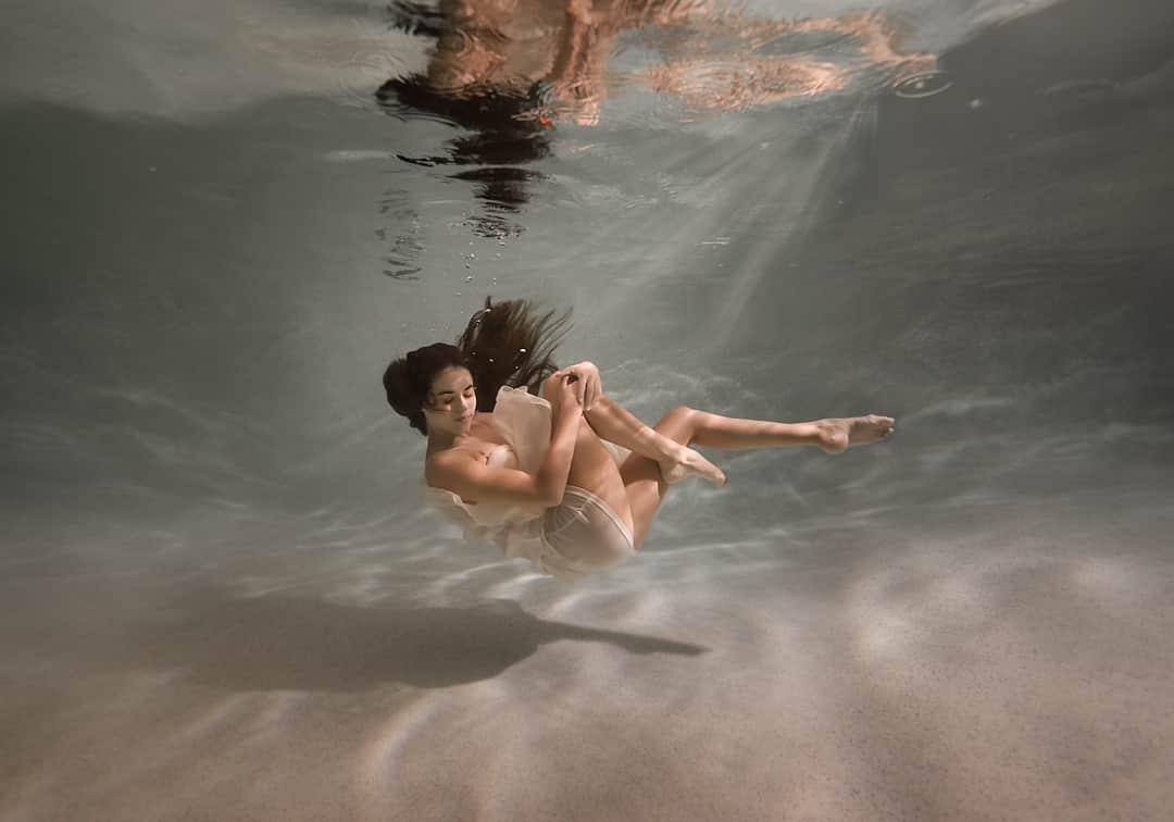 woman sinking underwater wearing a mini dress
