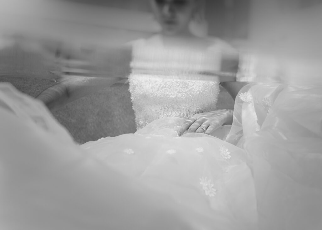 Underwater portrait of a bride in wedding dress, half in water, half out of water, over under shot, flowing white chiffon fabric, trash the dress shoot