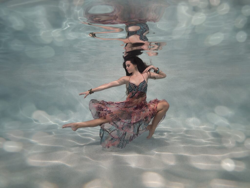Woman ballet dancing underwater in a swimming pool, with chunky jewellery and boho gypsy dress; Sunshine Coast, Australia