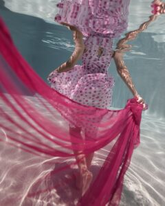 Underwater photo of a woman in a pink polka-dot dress, floating fabric, walking away