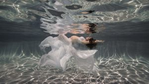 Pregnancy portrait underwater, maternity, woman floating on her back, wearing white flowing dress