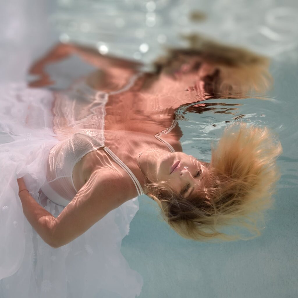Woman underwater lying back and looking at camera, blonde hair, floaty white chiffon dress, with watery reflections