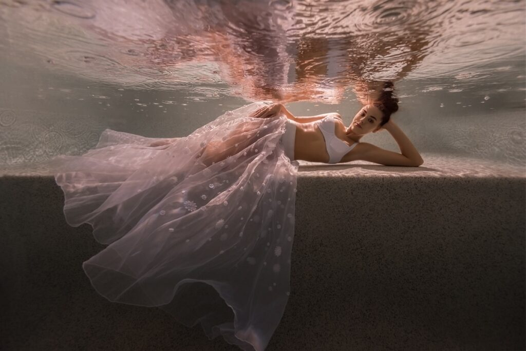 Beautiful woman wearing white sheer fabrics, reclining on a ledge underwater in a swimming pool