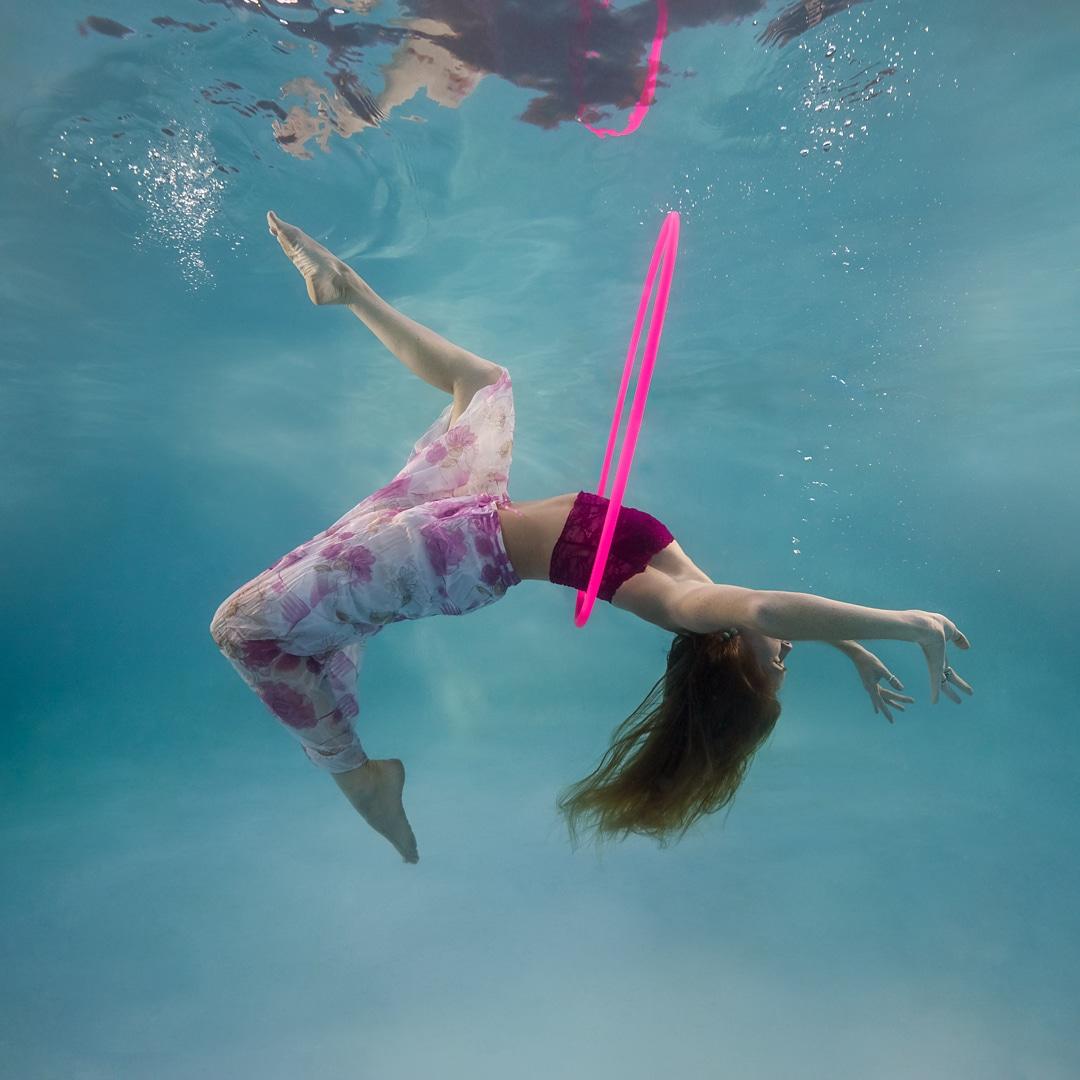 woman wearing pink and purple, hula hoop somersault dancing underwater