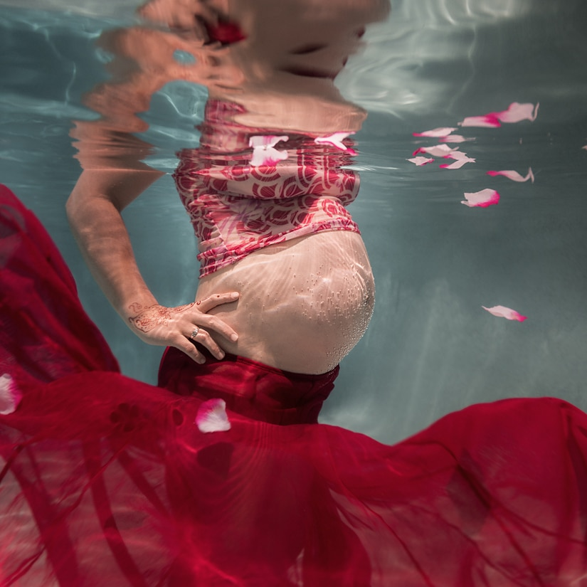 Pregnant Belly Underwater With Bubbles On Skin And Floating Flower Petals And Red Fabric And Henna Tattoo On Hand