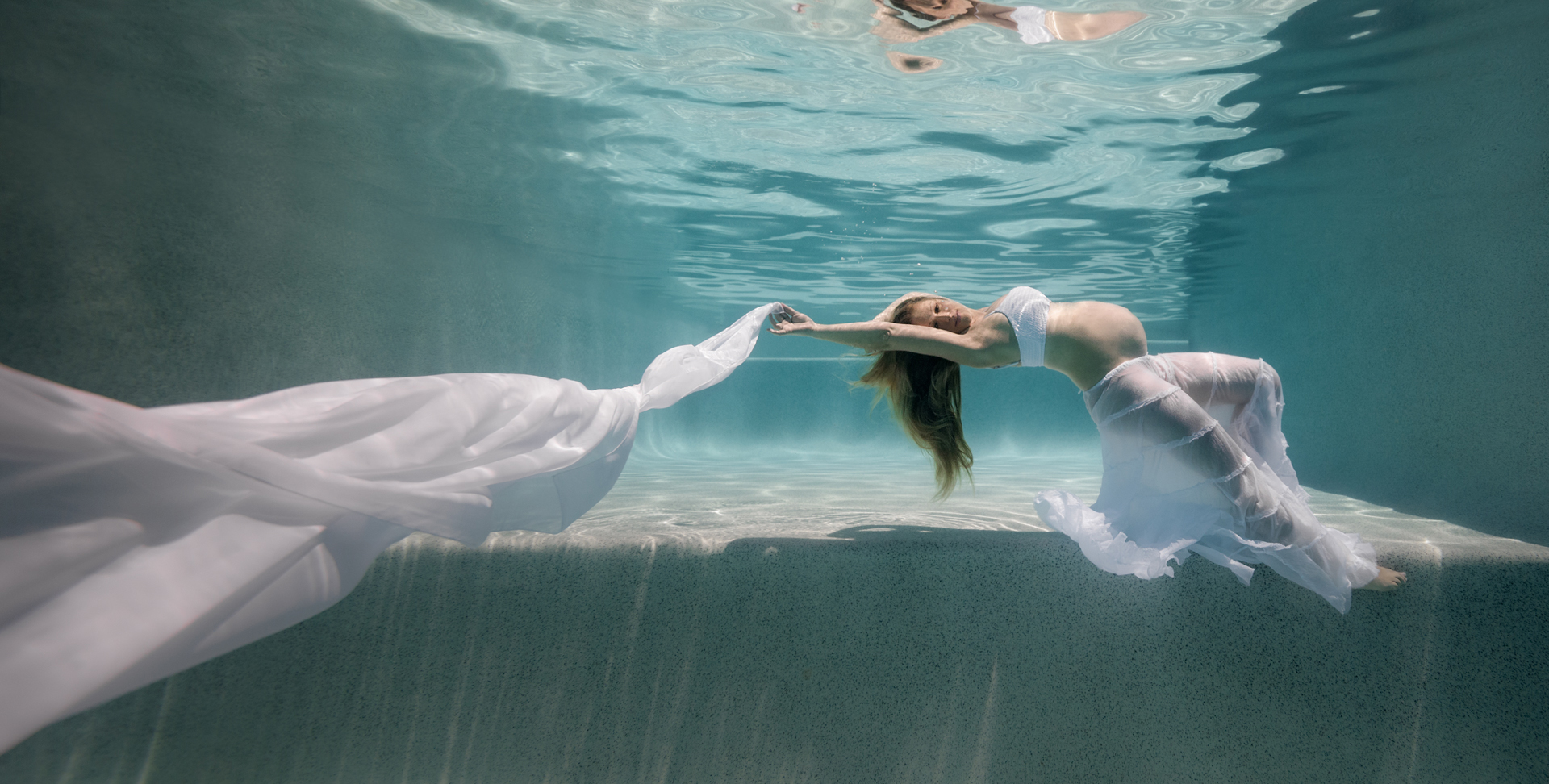 Underwater maternity portrait of a pregnant lady in a large swimming pool, wearing flowing white skirt and draping a long white chiffon scarf