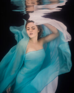 woman with chiffon floaty blue and white dress underwater with black background