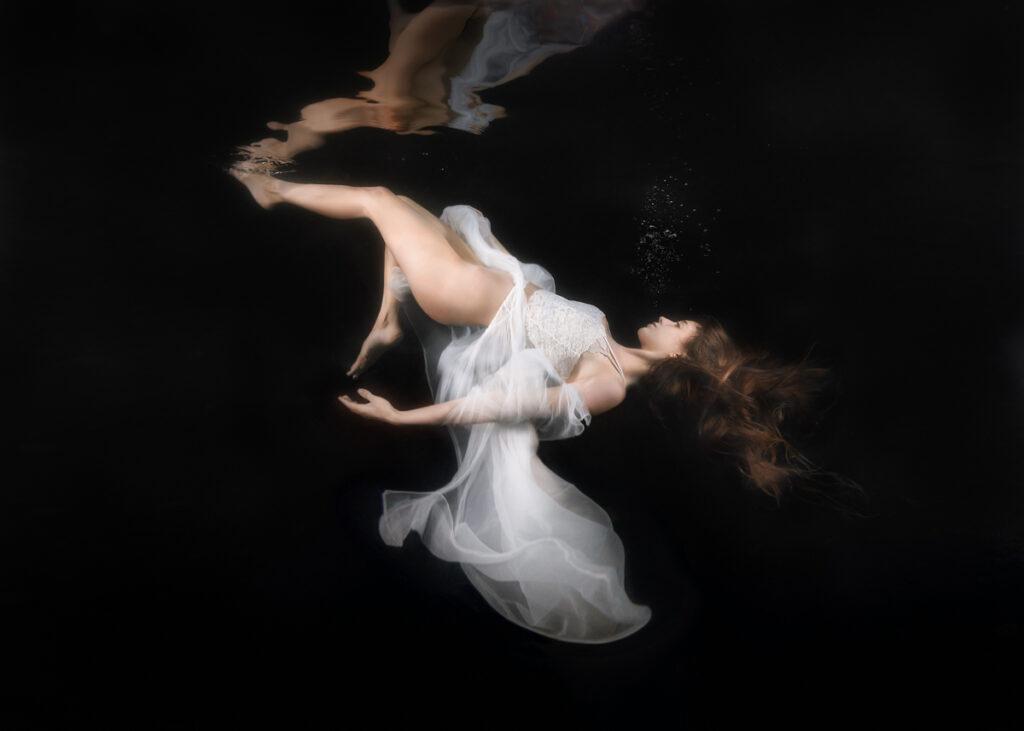 woman in white floaty gown, sinking underwater, black background, long hair, dreamlike