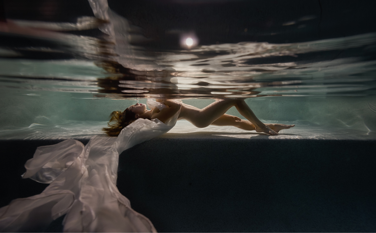 woman floating underwater at night with the moon showing above
