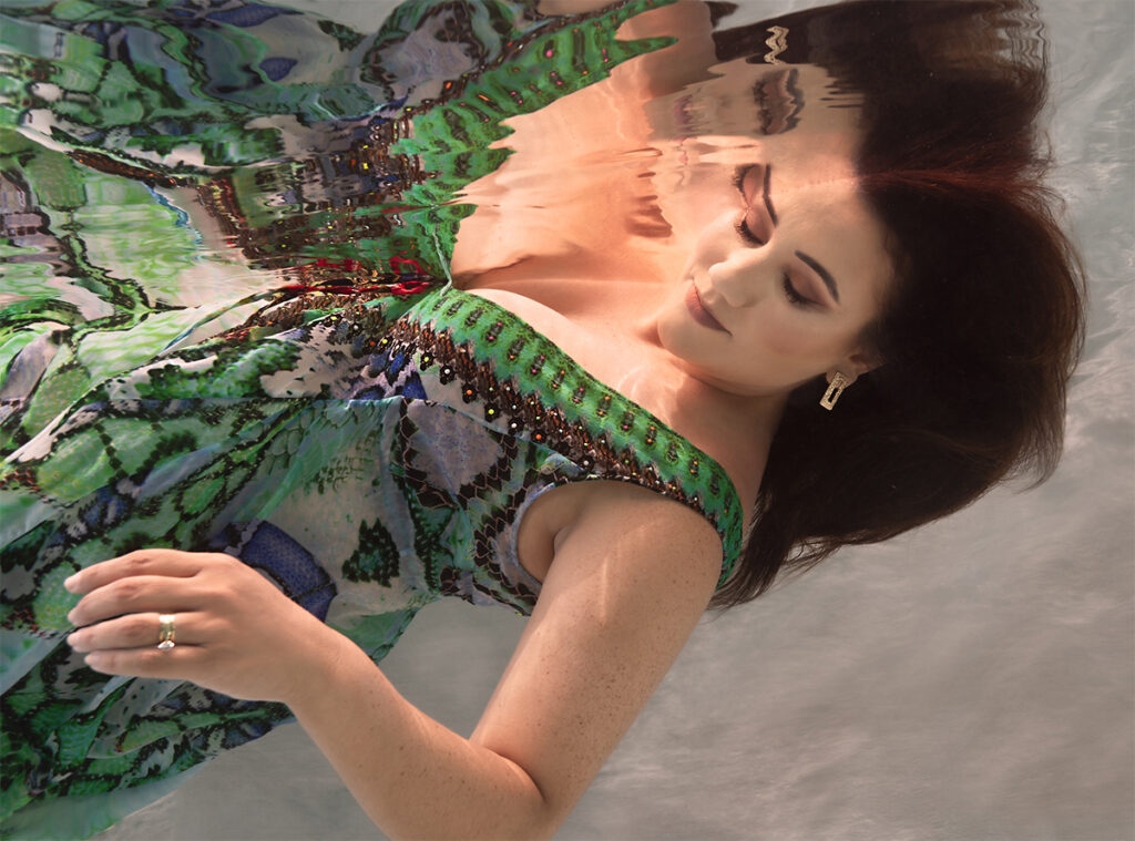 dark haired woman in beautifyl green patterened dress floating underwater