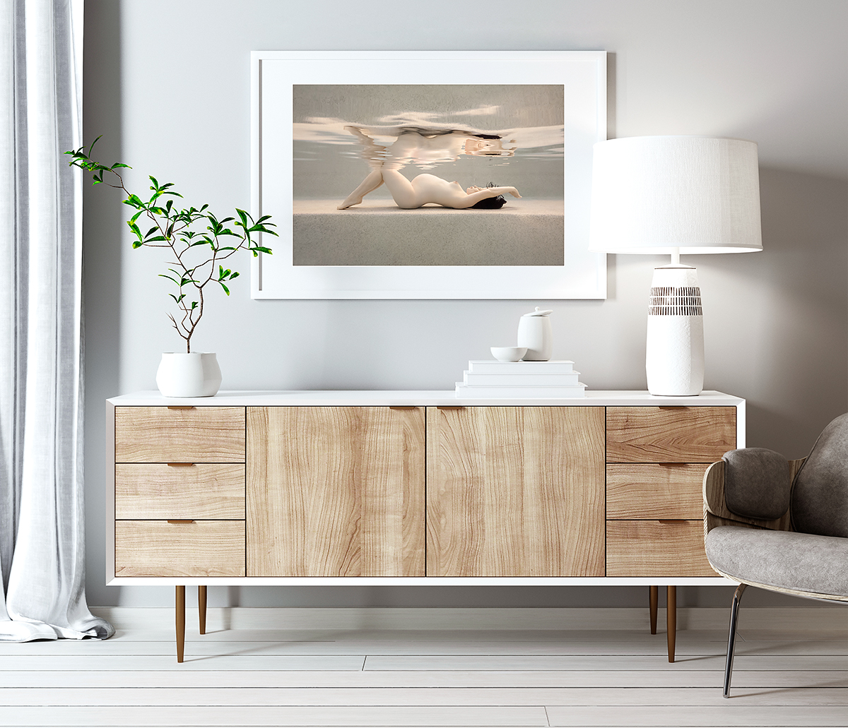 framed photo of a nude pregnant woman, displayed above a sideboard