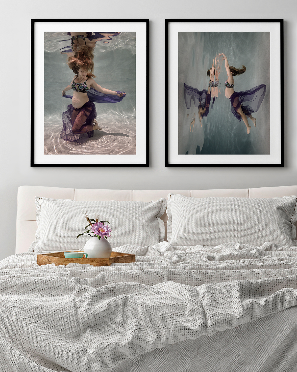 Pair of artworks of pregnant woman underwater, displayed over a bed with white bedding