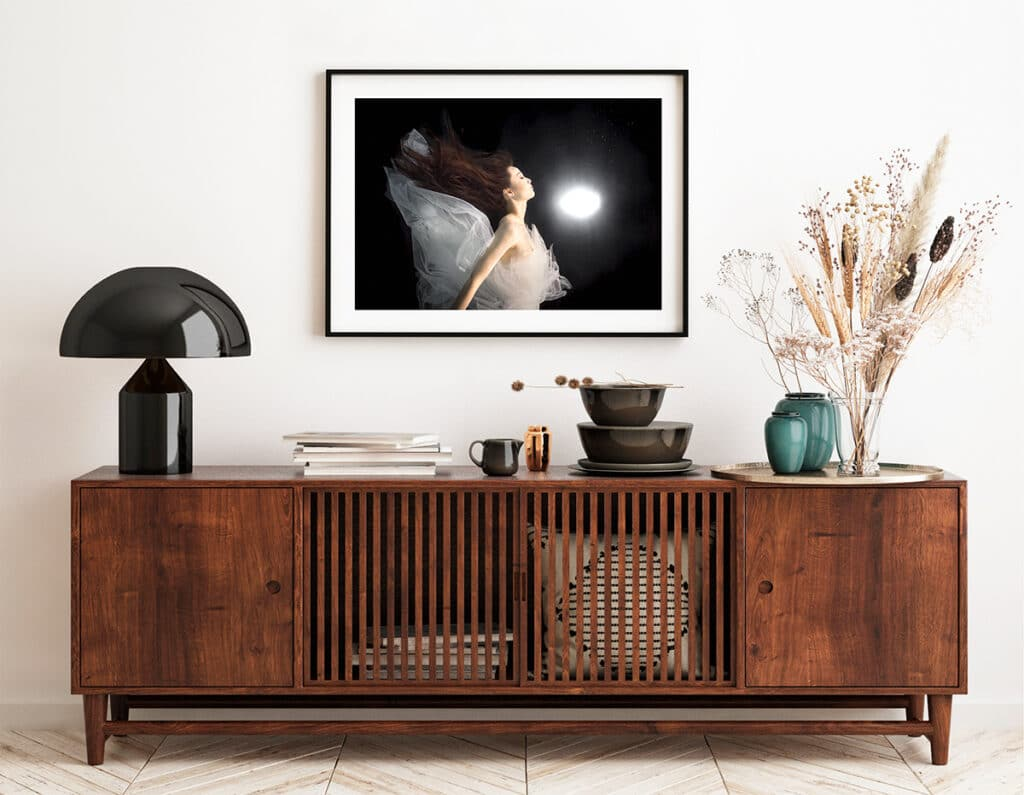 Underwater portrait wall art displayed above a stylish sideboard