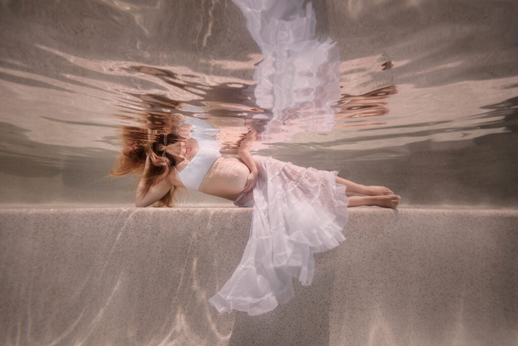 pregnant woman laying on her side underwater in a pool, wearing a white top and a white skirt