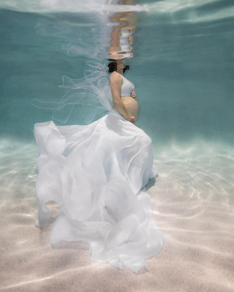 Underwater pregnancy portrait of a woman holding her belly and wearing a flowing white gown